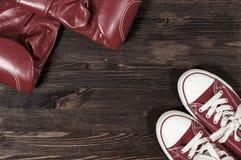 Gants de boxe rouges et espadrilles rouges sur une surface en bois Photos stock