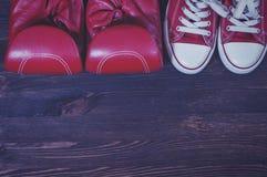Gants de boxe rouges et une paire d'espadrilles rouges sur un s en bois brun Photographie stock