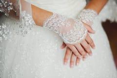 Gants de dentelle de mariage sur des mains de jeune mariée, plan rapproché images stock