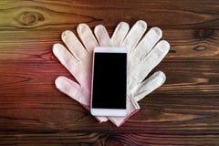 Gants de ménage, smartphone avec un écran noir sur le fond image stock