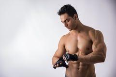 Gants de port d'homme musculeux de torse nu pour la séance d'entraînement images libres de droits