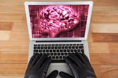 Gants de port de pirate informatique utilisant un ordinateur portable avec un cerveau rose sur le fond de bureau Image libre de droits