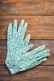 Gants en caoutchouc pour le travail de jardin sur un fond en bois brun images stock