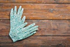 Gants en caoutchouc pour le travail de jardin sur un fond en bois brun image stock
