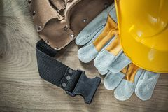 Gants en cuir de sécurité de ceinture de construction construisant le casque sur le woode Images stock