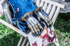 Gants et bouclier médiévaux de main en métal de chevalier sur la chaise en bois images libres de droits