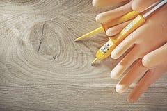 Gants isolants d'appareil de contrôle électrique sur le conseil en bois Image libre de droits