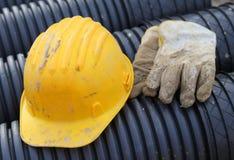 Gants jaunes de casque antichoc et de travail dans le chantier de construction Images libres de droits