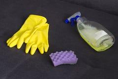Gants jaunes de nettoyage, une éponge et un détergent sur l'écran de divan photographie stock libre de droits