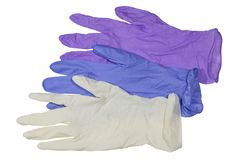 Gants médicaux colorés de latex sur le fond blanc photo libre de droits