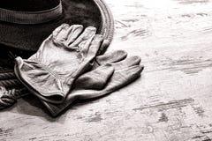 Gants occidentaux américains d'exploitation d'un ranch de rodéo sur le chapeau occidental photographie stock libre de droits
