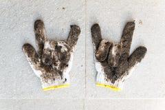 Gants sales poing l'AMOUR avec le sol d'argile après le jardinage sur la pierre Photos stock