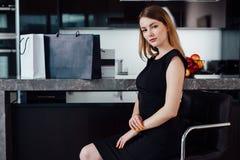 Ganzaufnahme der eleganten Frau mit dem angemessenen Haar, das schwarzes Kleid und die hohen Absätze herein sitzen auf einem Barh Stockbilder