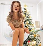 Ganzaufnahme der glücklichen Frau sitzend nahe Weihnachtsbaum Lizenzfreie Stockfotos