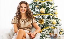 Ganzaufnahme der glücklichen Frau sitzend nahe Weihnachtsbaum Lizenzfreie Stockfotografie