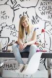 Ganzaufnahme der glücklichen Jugendlichen mit dem Skateboard, das auf Studie sitzt, verlegen zu Hause Stockbild