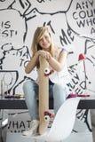 Ganzaufnahme der glücklichen Jugendlichen mit dem Skateboard, das auf Studie sitzt, verlegen zu Hause Lizenzfreies Stockbild