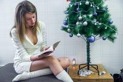 Ganzaufnahme der glücklichen jungen Frau, die nahe Weihnachtsbaum sitzt Stockfotos