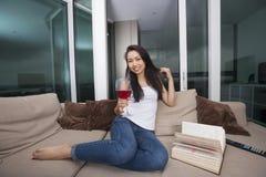 Ganzaufnahme der glücklichen jungen Frau, die Rotwein im Wohnzimmer isst Stockbild