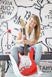 Ganzaufnahme der Jugendlichen mit der E-Gitarre, die auf Studie sitzt, verlegen zu Hause Lizenzfreie Stockbilder
