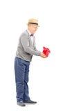 Ganzaufnahme des älteren Herrn Geschenk halten Stockfoto