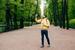 Ganzaufnahme des bärtigen jungen Mannes kleidete in der gelben Jacke, in Jeans und in schwarzer Kappe an, die Weg über dem grünen stockbild