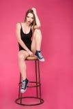 Ganzaufnahme des hübschen Mädchens sitzend auf Barhocker Stockfotos