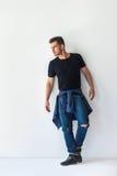 Ganzaufnahme des hübschen stilvollen Mannes, der am weißen wa sich lehnt Lizenzfreie Stockfotografie