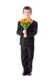 Ganzaufnahme des kleinen Jungen im Anzug mit Blumen Stockbild