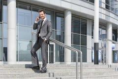 Ganzaufnahme des lächelnden antwortenden Handys des Geschäftsmannes bei der Stellung auf Schritten außerhalb des Büros Stockfotografie
