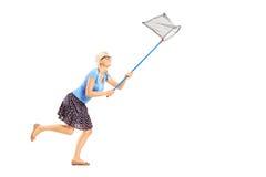 Ganzaufnahme einer Frau, die mit Schmetterlingsnetz läuft Stockfotos