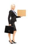 Ganzaufnahme einer jungen Frau im schwarzen Anzug, der einen PU hält Lizenzfreie Stockfotos
