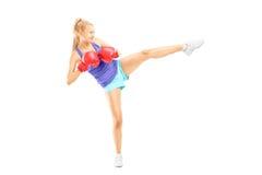 Ganzaufnahme einer jungen Frau mit Boxhandschuhe hittin Lizenzfreie Stockfotografie