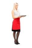Ganzaufnahme einer lächelnden blonden weiblichen Kellnerinholding Stockbild