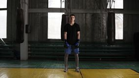 Ganzaufnahme einer männlichen Boxerstellung des dunkelhaarigen jungen Kaukasiers in einer altmodischen boxenden Turnhalle nahe de stock footage