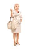 Ganzaufnahme einer reifen Frau, die mit einer Geldbeuteltasche aufwirft Lizenzfreie Stockbilder