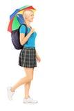 Ganzaufnahme einer Studentin, die mit Regenschirm geht Lizenzfreies Stockfoto