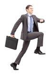 Ganzaufnahme eines Geschäftsmannes, der einen gewaltigen Schritt hin zu tut stockbild