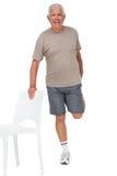 Ganzaufnahme eines glücklichen älteren Mannes, der Bein ausdehnt stockfoto