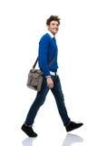 Ganzaufnahme eines glücklichen Gehens des jungen Mannes Lizenzfreies Stockfoto