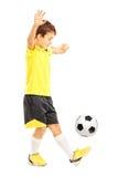 Ganzaufnahme eines Jungen in der Sportkleidung, die ein Fußballba schüttelt stockfotografie