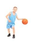 Ganzaufnahme eines Kindes, das mit einem Basketball spielt Stockbild