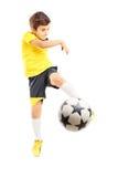 Ganzaufnahme eines Kindes in der Sportkleidung, die ein Fußballba schießt Stockfotografie