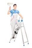 Ganzaufnahme eines männlichen Malers, der eine Rolle hält und stan Stockbild