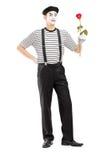 Ganzaufnahme eines männlichen Pantomimekünstlers, der eine Rosenblume hält Lizenzfreie Stockfotografie
