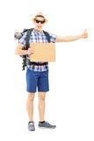 Ganzaufnahme eines männlichen Touristen mit Rucksack per Anhalter fahrend Stockbilder