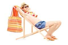 Ganzaufnahme eines Mannes, der auf einem Sonnenruhesessel genießt stockfotografie