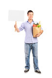 Ganzaufnahme eines Mannes, der eine Papiertüte und eine leere Wanne hält Stockfotografie