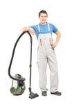 Ganzaufnahme eines Mannes in der Uniform, die mit einem Vakuumcl aufwirft Stockfoto