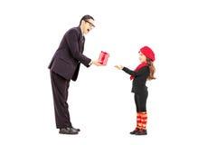 Ganzaufnahme eines Manngebens einem kleinen Mädchen vorhanden Lizenzfreie Stockbilder